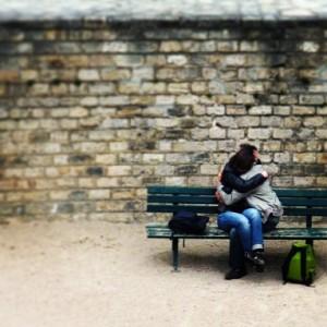 To elskende på en benk på den romerske arenaen i Paris.